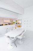 Dining area and open-plan kitchen in white, architect-designed house