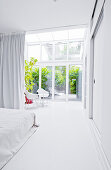 Schlafzimmer ganz in Weiß mit Glaswand zum Wintergarten