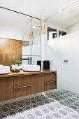 Elegant bathroom with walk-in shower, double walnut vanity, wall mirror and hexagonal floor tiles