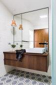 Elegant bathroom with walnut vanity, wall mirror and hexagonal floor tiles