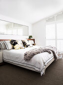 Double bed with pillows, large mirror above in white living room