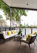 Elegant outdoor furniture on a covered, elevated terrace with a wooden deck
