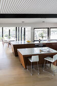 Elegant kitchen with breakfast bar, dining area in front of window front in open living room