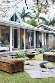 Vintage wooden benches with cushions, carpets and cushions in the garden in front of a wooden house with a veranda