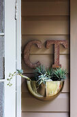 Golden plant bowl and vintage letters on wooden wall