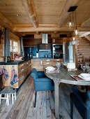 Set table in front of open-plan kitchen with wooden cupboards in log cabin
