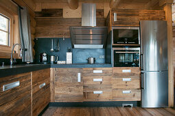 Modern kitchen with rustic wooden cupboards and stainless steel fridge