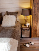 Table lamp with base made from twigs on trunk used as bedside table in bedroom