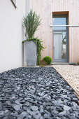 Bed of slate and gravel path in front garden leading to glass front door