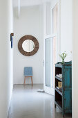 Blue chair and round mirror in bright hallway with glass wall