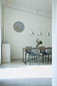 Delicate dining set below sloping ceiling in purist interior