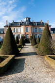 View of Château Les Aulnois between conical clipped hedges