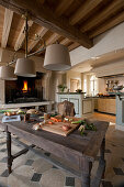 Rustic wooden table in traditional kitchen with open fireplace