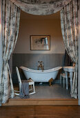 Free-standing bathtub in bathroom partitioned by curtains