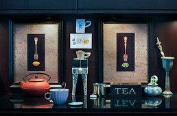 Teekanne und Tasse vor zwei beleuchteten Bildern mit Gabeln