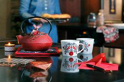 Tassen mit Vogelmotiv vor einer roten Teekanne aus Gusseisen