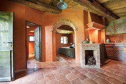 Mediterranean interior with terracotta floor tiles, fireplace and view into bedroom through arched open doorway