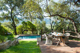 Rattan armchairs around set breakfast table on wooden terrace with swimming pool in background