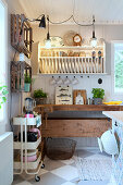 Plate rack above old workbench in country-house kitchen