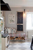 Chalkboards above bench with firewood below in country-house kitchen