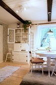 Kitchen dresser with open doors in country-house-style dining room