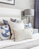 Pale grey, white and blue scatter cushions on double bed