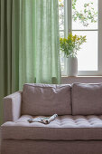 Magazine on grey sofa in front of window with green curtain