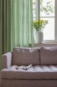 Zeitschrift auf grauem Sofa vor dem Fenster mit grünen Vorhängen