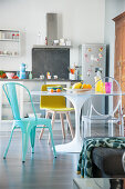 Round dining table and various chairs in front of open-plan kitchen