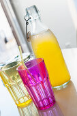 Pink and yellow drinking glasses in front of bottle of pop
