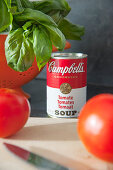 Tin of tomato soup next to basil in colander