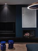 Open fireplace in dark blue and black living room