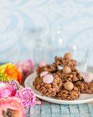 Easter arrangement of chocolate cornflake cakes on plate amongst ranunculus flowers