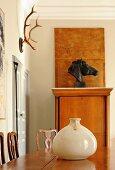 Edelholztisch mit Keramikgefäß vor Pferdekopf-Büste und Jagdtrophäe