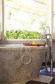 Massive Marmor-Badewanne mit Standarmatur und nostalgischem Flair vor offenem Badfenster