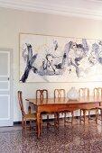 Langer Edelholztisch mit Stühlen vor modernem Gemälde und historischem Flair