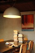 Large hemispherical lamp above stacked books on dining table