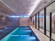 Elegant indoor swimming pool with glass sliding walls