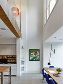 Open-plan kitchen with dining area in high-ceiling room with gallery level