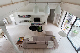 View down into bright living room with white floor