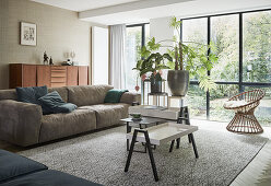 Nest of coffee tables in living room with glass wall