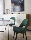 Chairs upholstered in dark green at dining table in front of sideboard with glossy white front