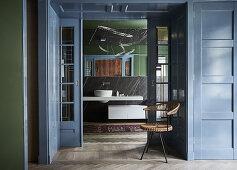 Chair in wood-panelled doorway with sliding doors leading into bathroom