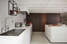 Modern, open-plan kitchen with white base units and no wall units