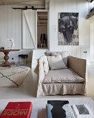 Hussensessel vor holzverkleideter Wand und Zugang zum Schlafzimmer im Loft