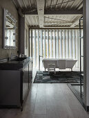 Metal washstand and free-standing bathtub in loft-apartment bathroom with vertical louvre blinds
