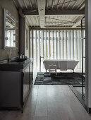 Metall-Waschtisch und frei stehende Badewanne im Loft-Badezimmer mit Vertikal-Lamellen