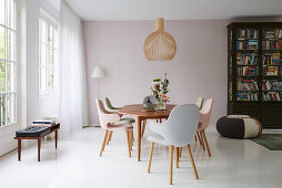 Chairs with pastel upholstery around dining table on white floor