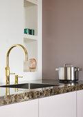Goldene Armaturen an der Spüle in minimalistischer Küche