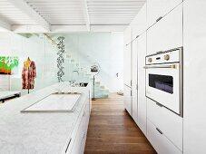 Einbauküche mit weissen Fronten und Kücheninsel mit Kochfeld